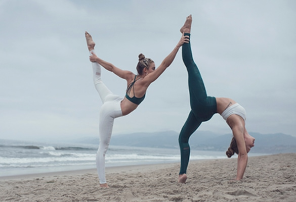 Duo females in a yoga pose on the beach